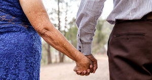 Older Latino couple walking in the park